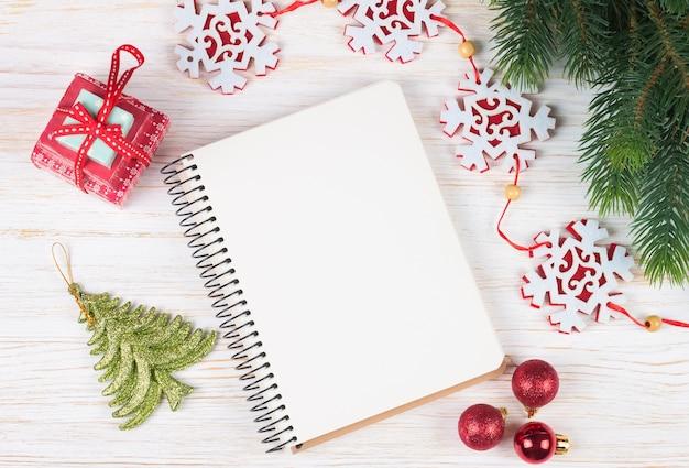Kompozycja świąteczna. ozdoby świąteczne, wianek, zegar, prezent i pusty notatnik na białym tle drewnianych.