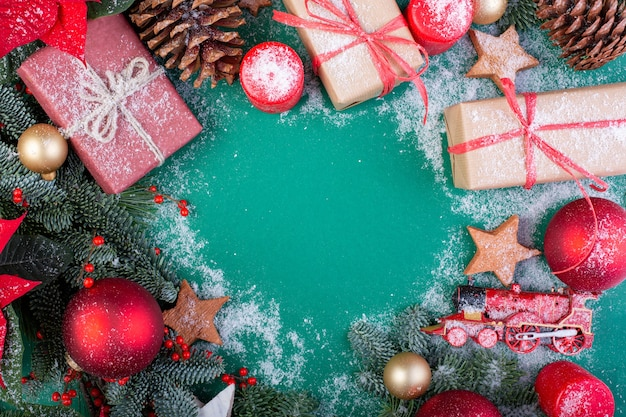 Kompozycja świąteczna. ozdoby świąteczne zielone, gałęzie jodły z pudełka na prezenty zabawki na zielonym tle. leżał na płasko, widok z góry, miejsce na kopię.