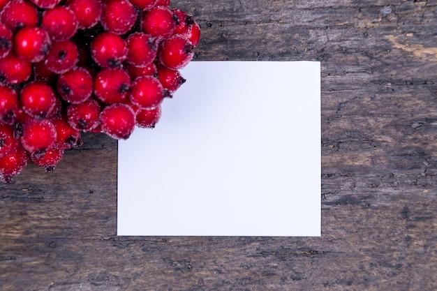 Kompozycja świąteczna. papier puste z gałęzi głogu jarzębiny z jagodami na drewnianym tle