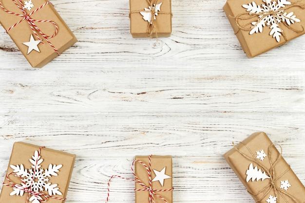 Kompozycja świąteczna. prezent na boże narodzenie, dzianinowy koc, płatek śniegu, gwiazda i dekoracyjne cgristmas drzewo na drewnianym białym. leżał płasko, widok z góry