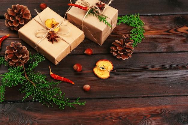Kompozycja świąteczna. prezent na boże narodzenie, koc z dzianiny, szyszki, gałęzie jodły na drewniane tła.