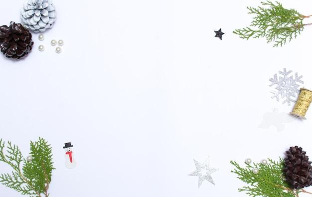 Kompozycja świąteczna. prezent na boże narodzenie, szyszki, gałęzie jodły na drewniane białe tło