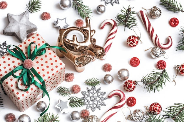 Kompozycja świąteczna. prezenty, gałęzie jodły, czerwone dekoracje na białej ścianie. koncepcja zima, nowy rok. układ płaski, widok izometryczny