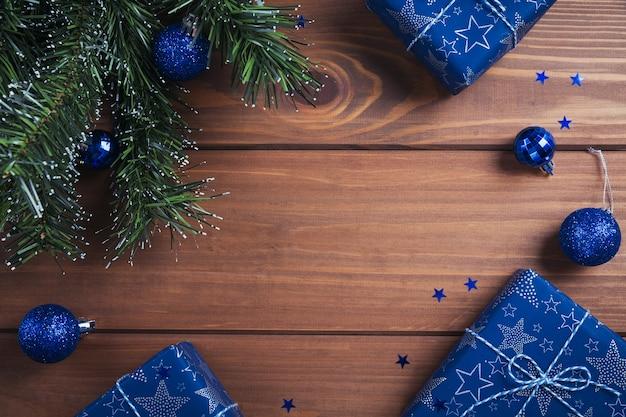 Kompozycja świąteczna. prezenty, gałęzie jodły, niebieskie dekoracje na drewnianych. koncepcja wakacje boże narodzenie, zima, nowy rok. leżał na płasko, widok z góry, miejsce na kopię
