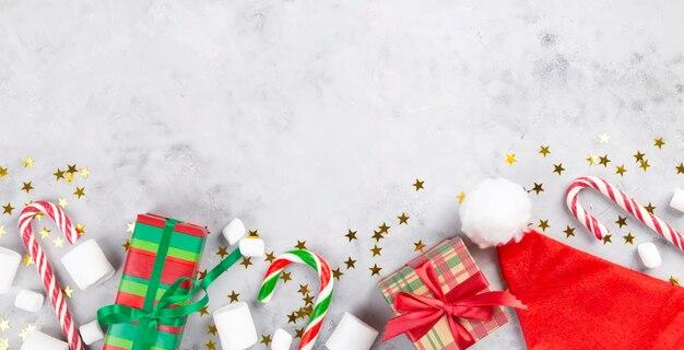 Kompozycja świąteczna. prezenty, karmelowa laska, ptasie mleczko, święty mikołaj na szarym betonowym tle z błyszczącymi gwiazdami.