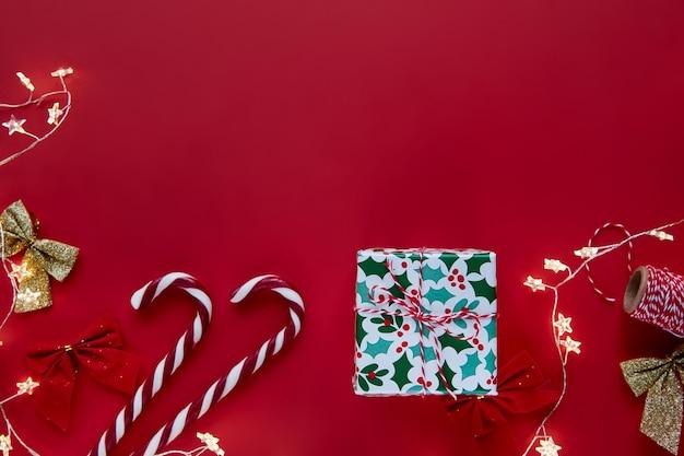 Kompozycja świąteczna. prezenty, prezenty owinięte wstążką, światła, ozdoby laski cukierków na czerwonym tle. zima, nowy rok mieszkanie świeckich, widok z góry, miejsce. szablon makiety projektu tekstu karty z pozdrowieniami