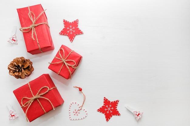 Kompozycja świąteczna. prezenty, szyszki jodły, czerwone dekoracje na białym tle.