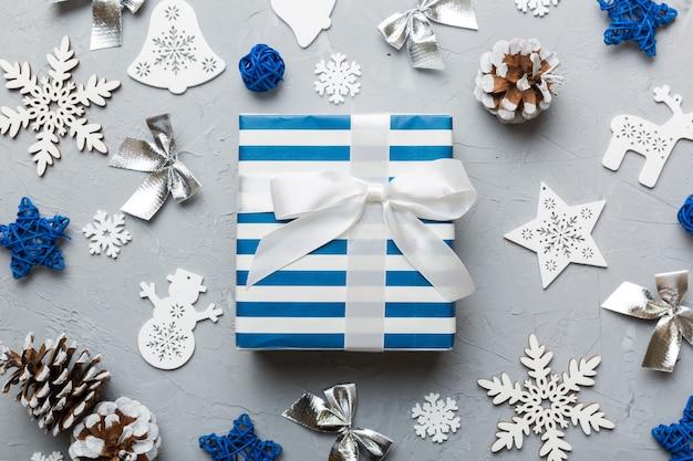 Kompozycja świąteczna. pudełko na prezenty z dekoracjami sylwestrowymi na kolorowym tle. boże narodzenie, zima, koncepcja nowego roku. płaski świeckich, widok z góry, kopia przestrzeń.