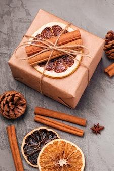 Kompozycja świąteczna. pudełko prezentowe, ozdoby z cynamonu, anyżu, suszonych owoców i szyszek na szarej powierzchni. widok pod kątem