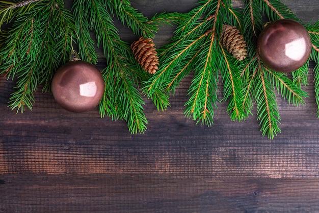 Kompozycja świąteczna. rama jodła rozgałęzia się i piłki na ciemnym nieociosanym drewnianym tle. boże narodzenie, ferie zimowe, koncepcja nowego roku. widok z góry
