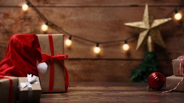 Kompozycja świąteczna. santa hat i pudełka na prezenty świąteczne na drewnianym stole.