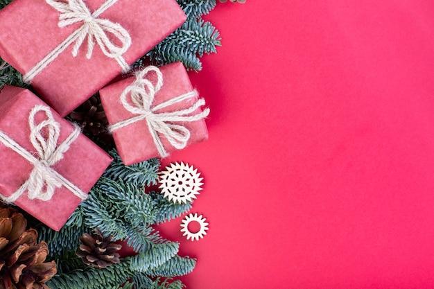 Kompozycja świąteczna. świąteczne dekoracje czerwone, gałęzie jodły z pudełka na prezenty zabawki na czerwonym tle. leżał na płasko, widok z góry, miejsce na kopię.