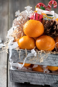 Kompozycja świąteczna. świeże mandarynki i nowy rok zabawki w pudełku na starym drewnianym