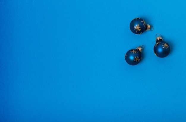 Kompozycja świąteczna. trzy niebieskie kule ze złotymi gwiazdami na niebieskim tle. płaski układanie, widok z góry