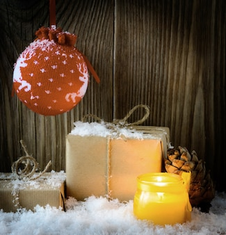 Kompozycja świąteczna w stylu vintage z pudełkami prezentowymi owiniętymi w papier pakowy i świecą