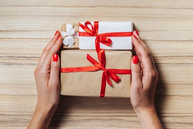 Kompozycja świąteczna. widok z góry, płaski układ. kobiece dłonie z czerwonymi polerowanymi paznokciami trzymające pudełka owinięte w papier rzemieślniczy i ozdobione satynową wstążką na drewnianym stole.