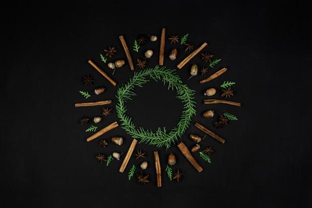 Kompozycja świąteczna. wieniec z gałęzi sosny, laska cynamonu, anyż, żołędzie na czarnym tle. leżał płasko, widok z góry, miejsce, kwadrat
