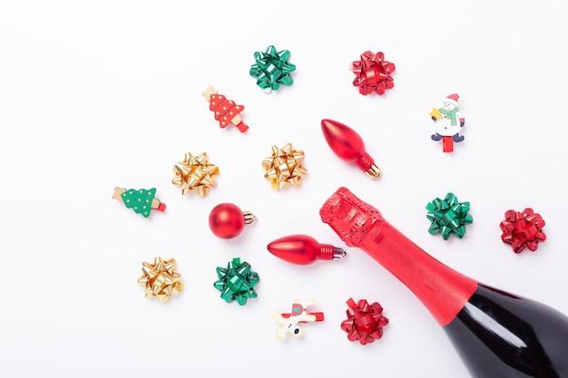 Kompozycja świąteczna z butelką szampana oraz kolorowymi kokardkami i żarówkami