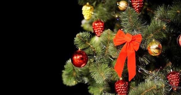 Kompozycja świąteczna z choinką, ozdoby świąteczne i duża czerwona kokarda