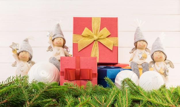 Kompozycja świąteczna z czerwonymi pudełkami, aniołami i jodłą