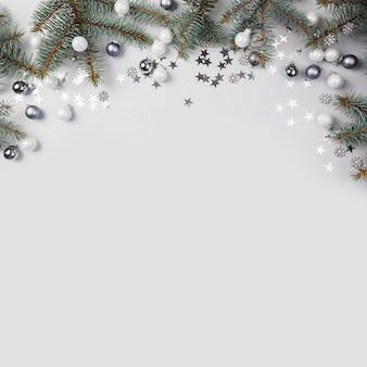 Kompozycja świąteczna z jodłą gałęzie drzewa, srebrne kulki na szaro. karta wesołych świąt. zimowe wakacje. .