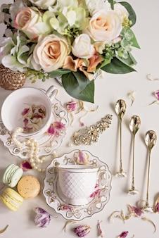 Kompozycja świąteczna z kwiatami i białymi filiżankami do herbaty