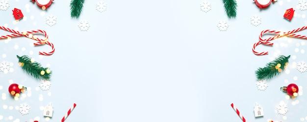 Kompozycja świąteczna z miejscem na tekst. zabawki świąteczne, model samochodu, trzcina cukrowa, czerwone kulki, drewniane domy z brokatowymi konfetti na niebieskim tle