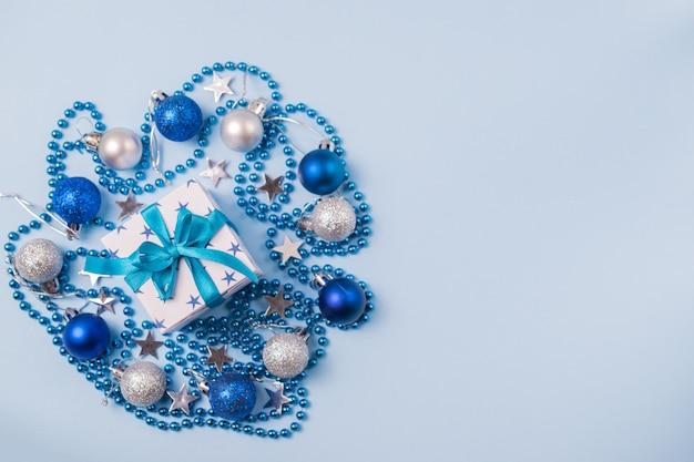 Kompozycja świąteczna z pudełkiem prezentowym z piękną kokardką, koralikami, bombkami i gwiazdkami