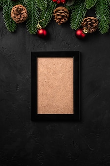 Kompozycja świąteczna z pustą ramką na zdjęcia. kolorowa ozdoba, ozdoby z szyszek i igieł jodłowych. makiety szablonu karty pozdrowienia