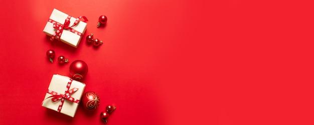 Kompozycja świąteczna z świątecznymi czerwonymi pudełkami i czerwonymi wstążkami i małymi kulkami na czerwono.
