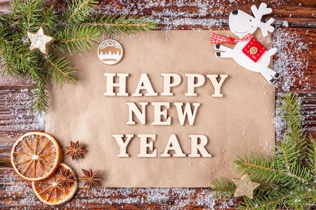 Kompozycja świąteczna z tekstem na papierze szczęśliwego nowego roku w środku ramy.