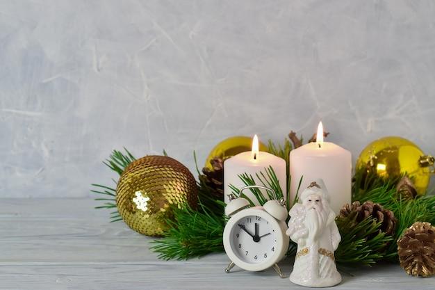 Kompozycja świąteczna z żółtymi bombkami, budzikiem i mikołajem