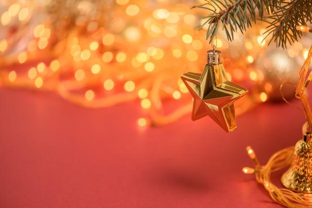 Kompozycja świąteczna złota gwiazda wisi na świerkowej gałęzi na czerwonym tle