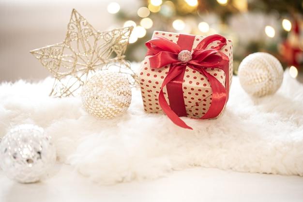 Kompozycja świątecznego prezentu i noworocznej dekoracji na jasnym tle z gerland światełkami.