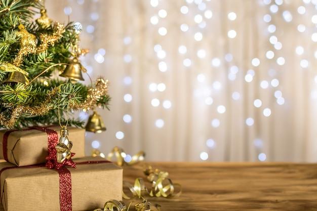 Kompozycja świątecznego stołu do wiadomości z ferii zimowych. choinka, prezenty, szyszki, bombki, lampki świąteczne i gwiazdy na ładnym bokeh.