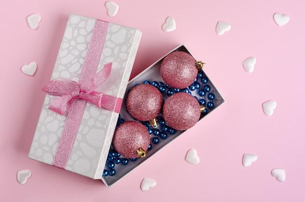 Kompozycja świąteczno-noworoczna. otwarte pudełko z bombkami i niebieską girlandą w pastelowym różu. płaskie świeckie miejsce. .