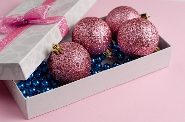 Kompozycja świąteczno-noworoczna. pudełko z bombkami w pastelowym różu. płaskie świeckie miejsce. .