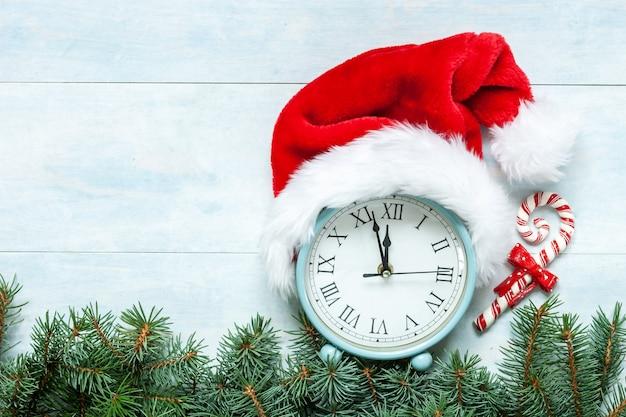 Kompozycja świąteczno-noworoczna z zegarem w czapce mikołaja pokazującym wigilię święta i personel mikołaja. widok z góry, z bliska na jasnoniebieskim tle.