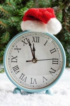 Kompozycja świąteczno-sylwestrowa z zegarem w czapce mikołaja pokazującym wigilię świąt