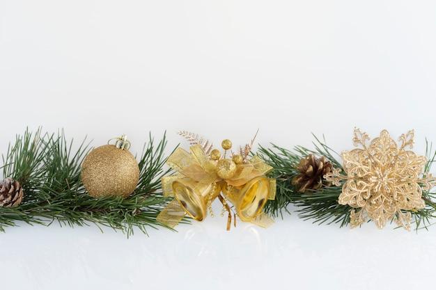 Kompozycja świątecznych dekoracji złote bombki, płatek śniegu, dzwonki i szyszki z gałęziami sosny