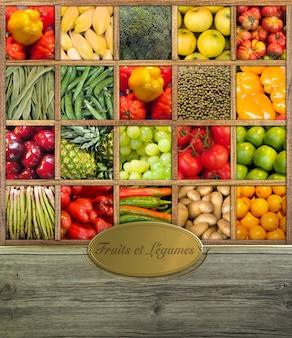 Kompozycja świeżych owoców i warzyw oprawiona w drewno ze złotą etykietą w języku francuskim
