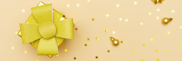 Kompozycja sylwestrowa bombki złote ozdoby i pudełko z cukierkami w postaci złotych s...