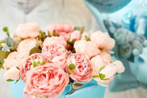Kompozycja sztucznych różowych piwonii w niebieskim pudełku. pocztówka