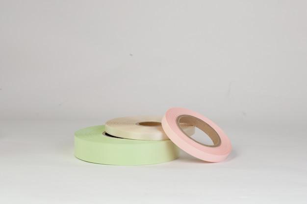 Kompozycja trzech zwojów satynowych wstążek w kolorze różowym zielonym beżowym na metki lub branding na białym tle