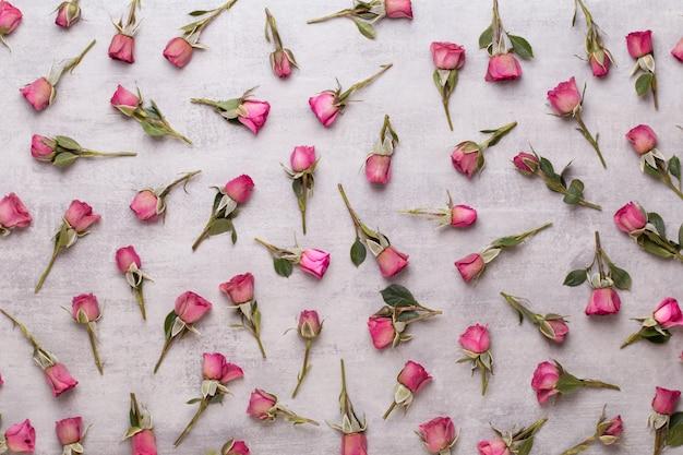 Kompozycja walentynki kwiaty. rama wykonana z różowej róży na szarym tle.