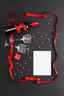 Kompozycja walentynkowa. wino i dwie szklanki, prezent i pusty arkusz na życzenie, prezent i czerwone serca