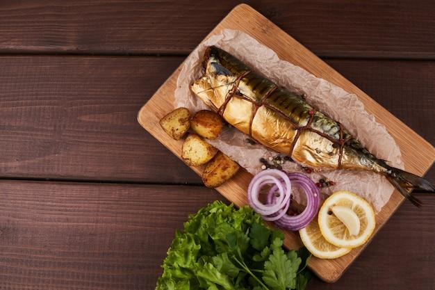 Kompozycja wędzona ryba makrela z ziemniakami udekorowanymi cytryną zieleniną cebulą podawana na drewnianej płycie talerz widok z góry