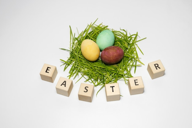 Kompozycja wielkanocna, jajka na zielonej trawie na białym tle, obok kostki umieszczone słowo wielkanoc. jajka są pomalowane naturalnymi barwnikami.