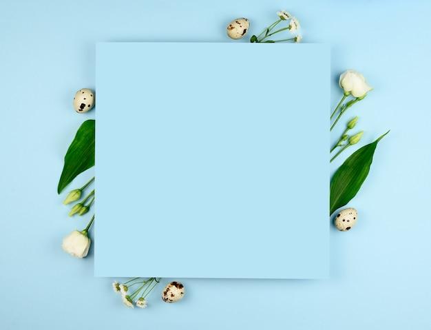 Kompozycja wielkanocna. pisanki, kwiaty, puste kartki papieru na pastelowym niebieskim tle. białe kwiaty. leżał na płasko, widok z góry, kopia przestrzeń, makieta.