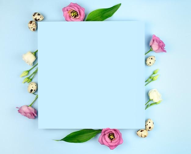 Kompozycja wielkanocna. pisanki, kwiaty, puste kartki papieru na pastelowym niebieskim tle. leżał na płasko, widok z góry, kopia przestrzeń, makieta.